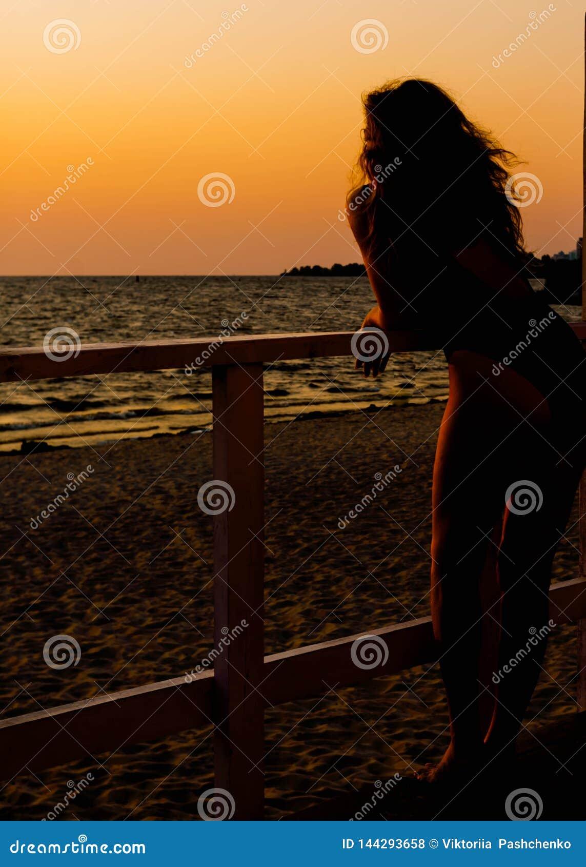 Kvinnakontur i baddräkt med flödande håranseende vid havet