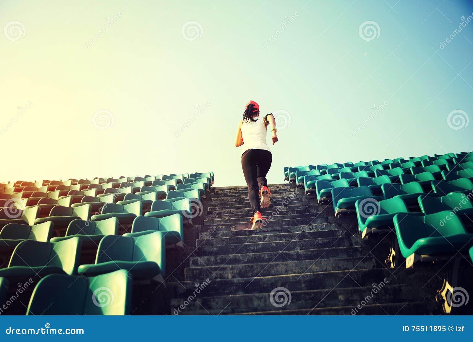 Kvinnalöpareidrottsman nen som är rinnande upp på trappa