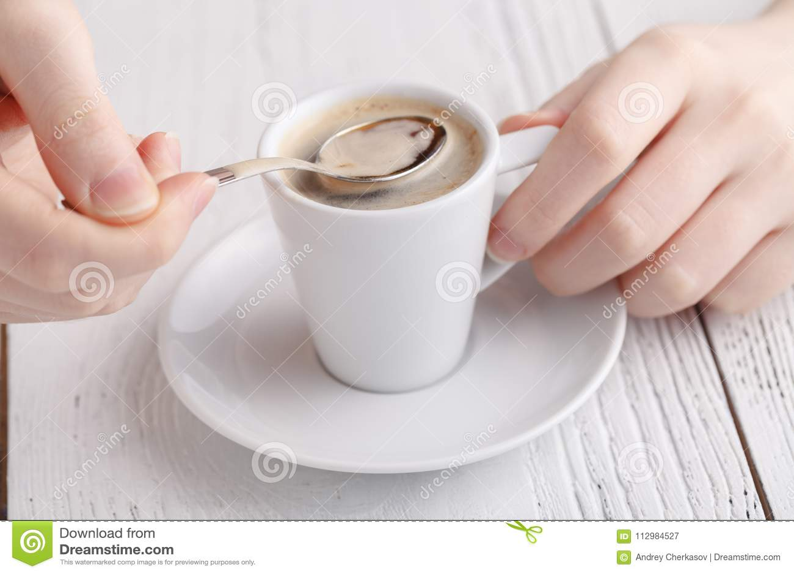 Kvinnan är hållande en kupa av kaffe