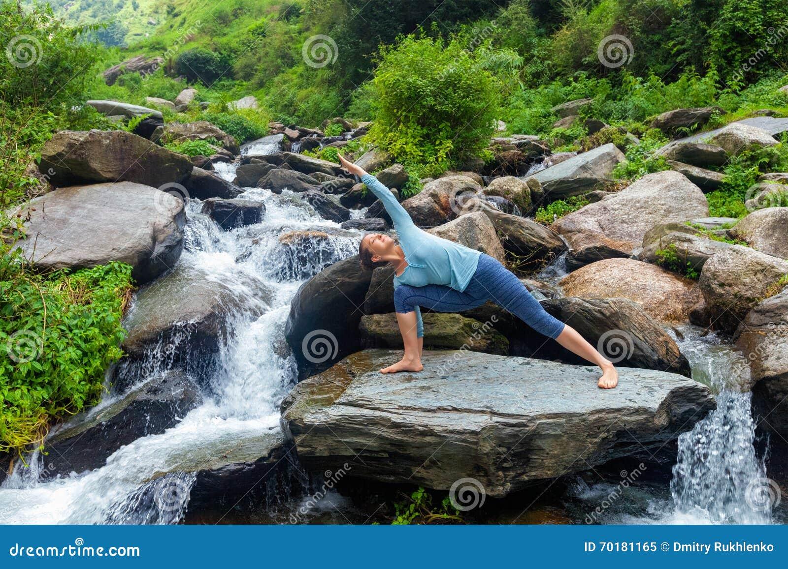 Kvinnan öva yogaasanaen Utthita Parsvakonasana utomhus