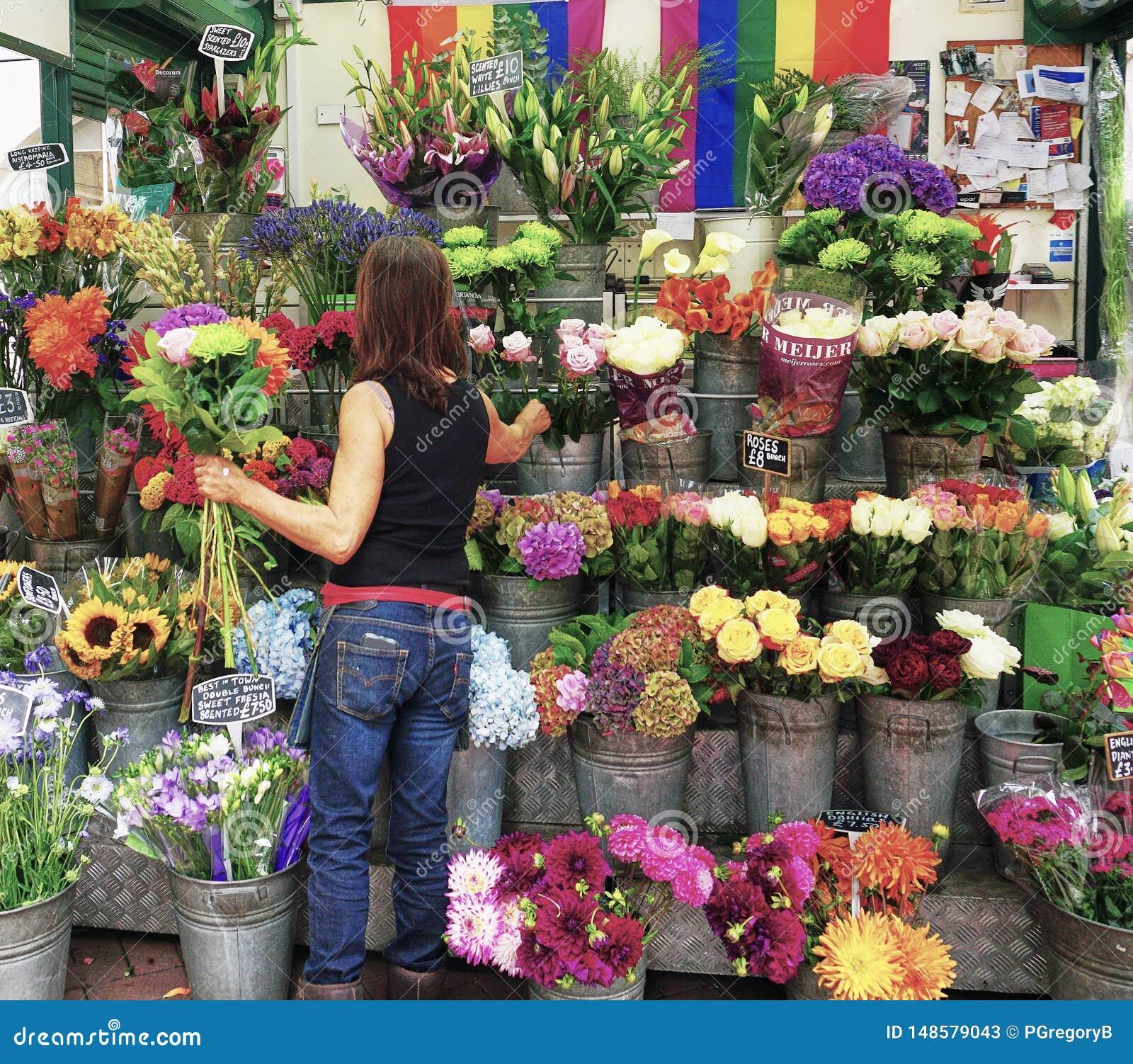 Kvinnan ansar till hennes blommakiosk i London, England