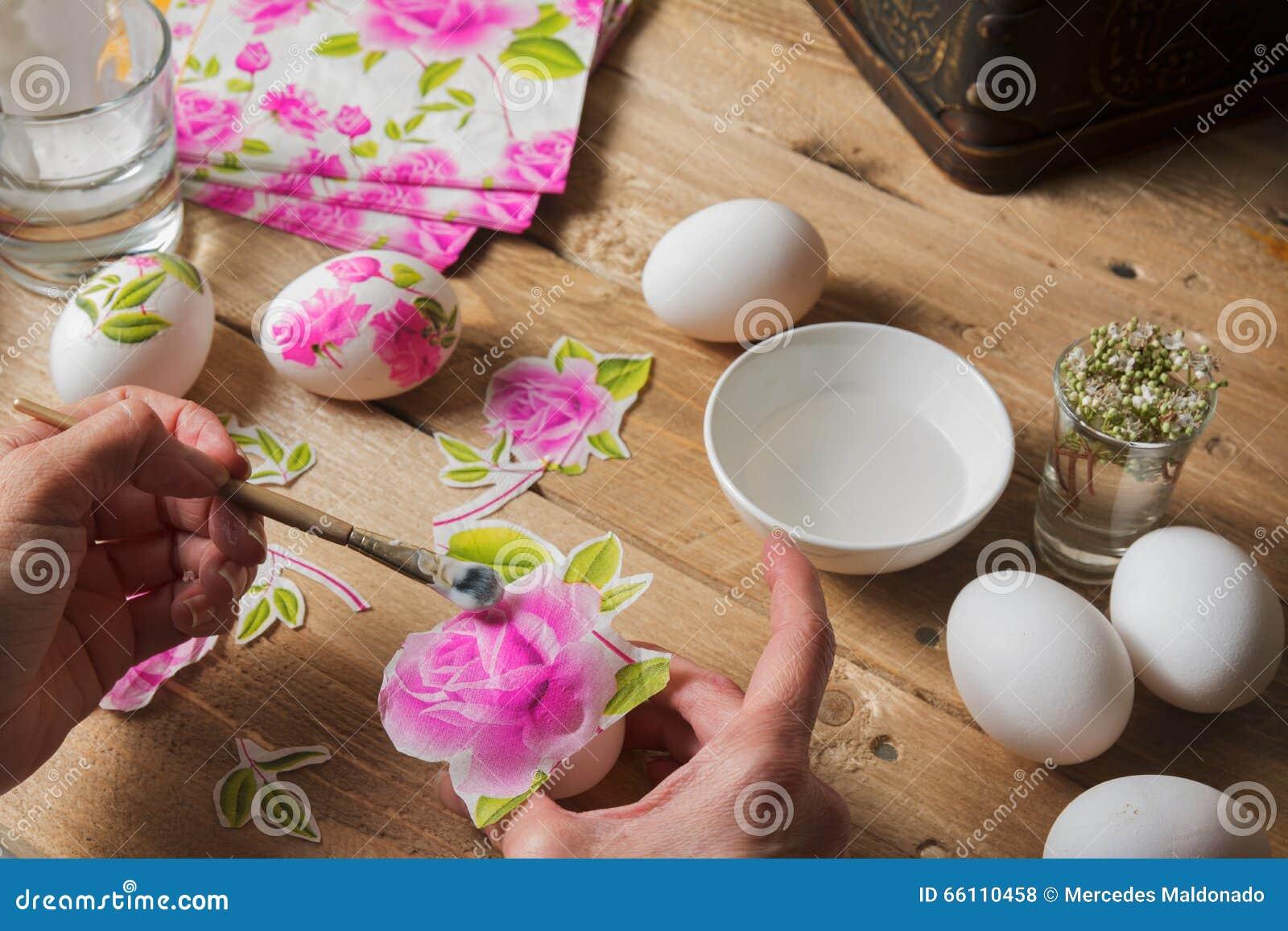 Kvinnan applicerar lim på det kulöra påskägget, teknik av decoup