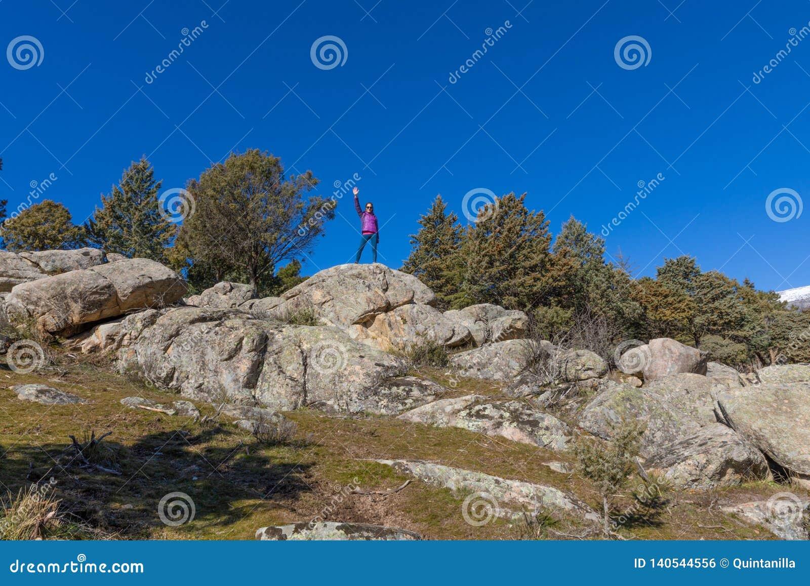 Kvinnan av vaggar överst att salutera med handen upp i berg