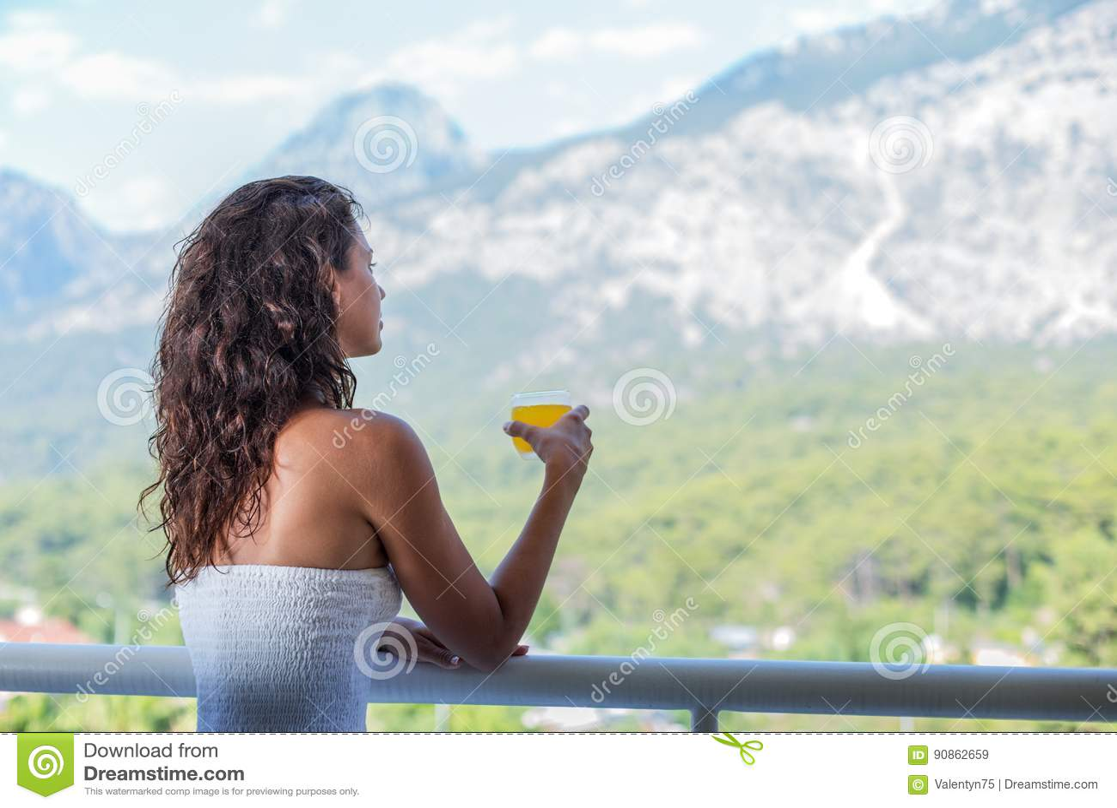 Kvinnan dricker orange fruktsaft på hotellbalkongen