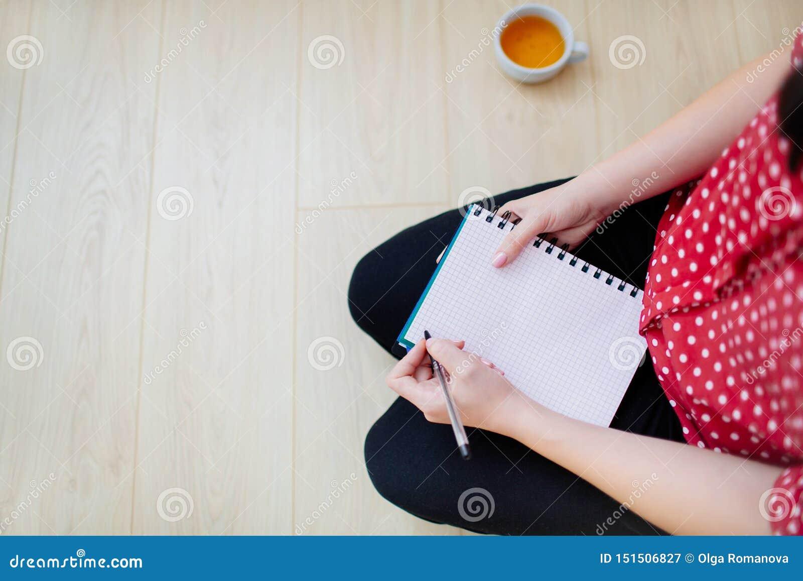 Kvinnan får klar att skriva i en notepad