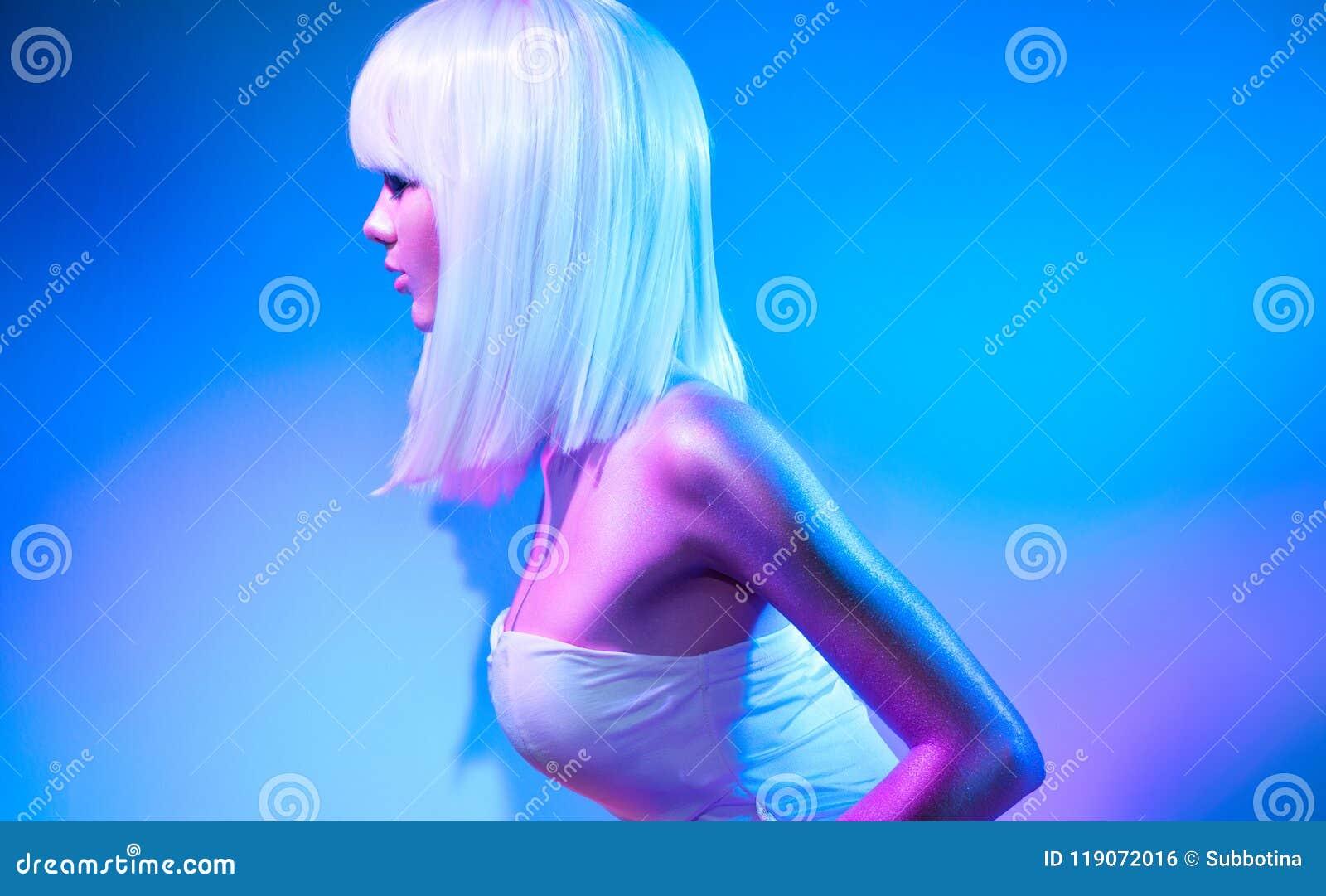 Kvinnan för modemodellen i färgrikt ljust mousserar och neonljus som poserar i studio