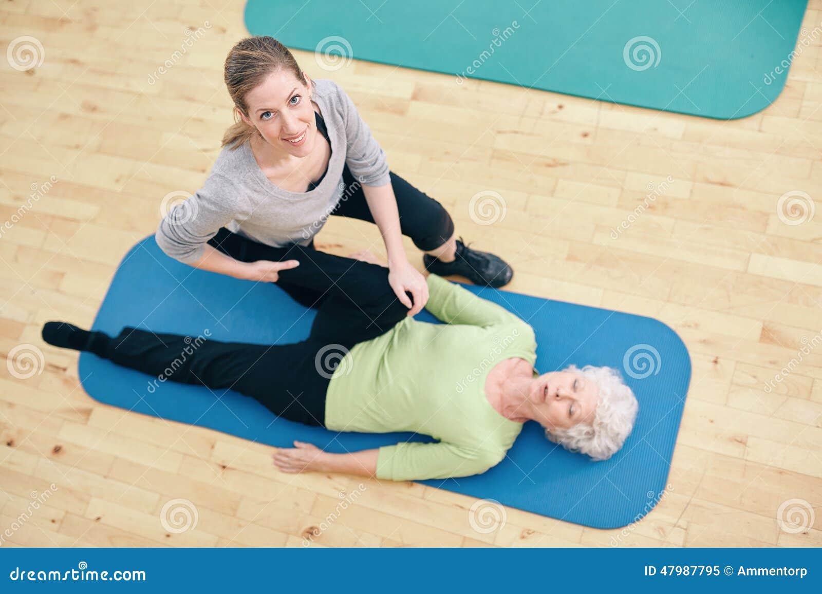 Kvinnan för portionen för den fysiska terapeuten lägger benen på ryggen den höga elasticiteter
