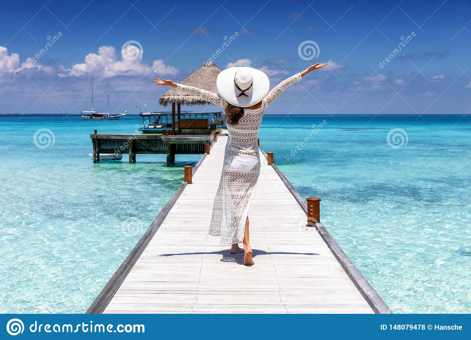 Kvinnan g?r p? en tr?brygga ?ver tropiskt vatten av de Maldiverna ?arna