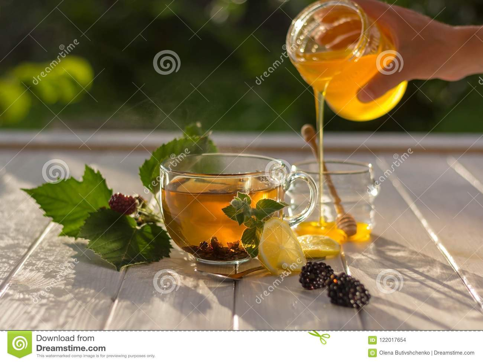 Kvinnan gör te och hällande honung