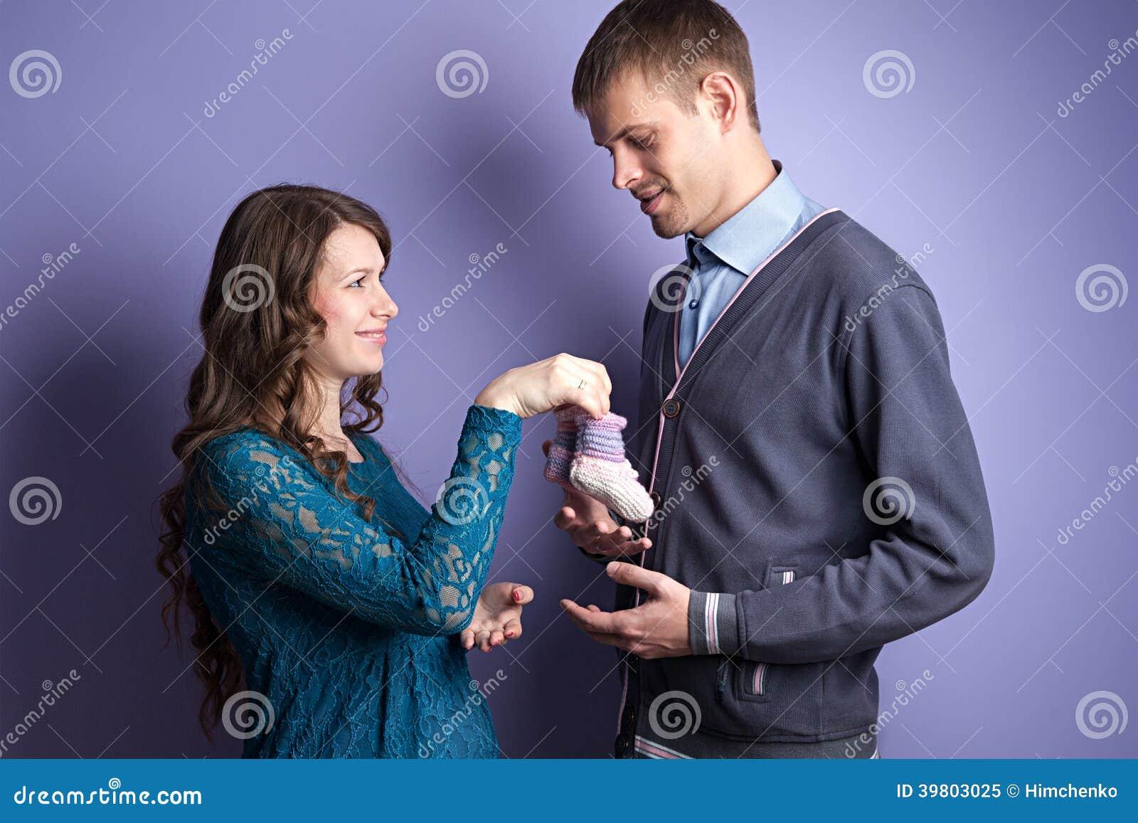 Kvinnan ger den framtida baby sens barnsockor till hennes man