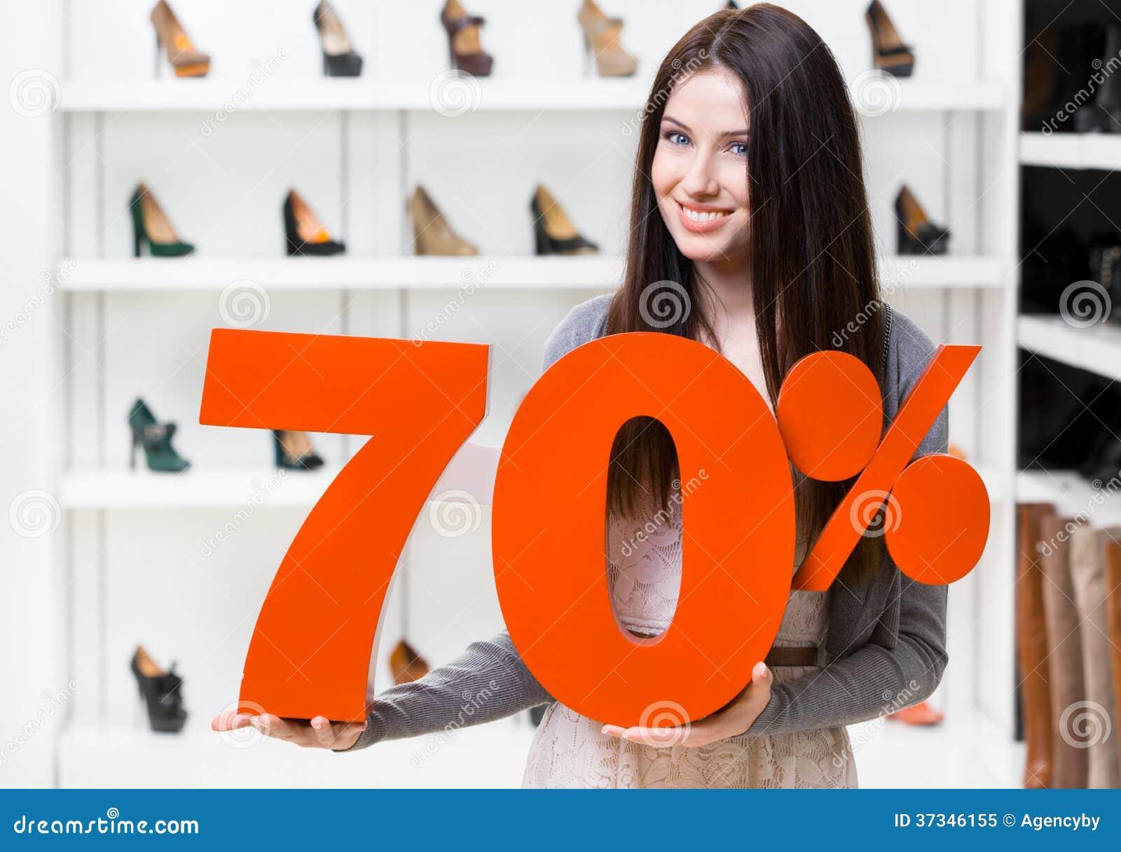 Kvinnan håller modellen av den 70  försäljningen på skor