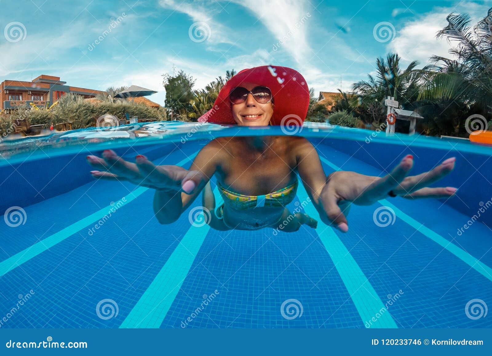 Kvinnan har en gyckel i simbassäng