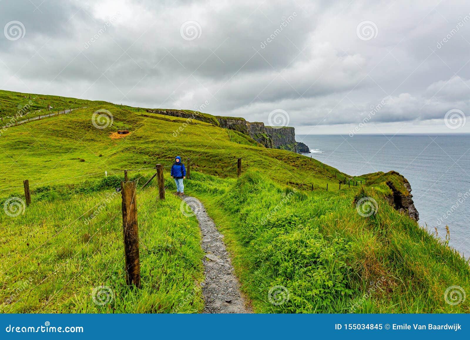 Kvinnan i blått omslag som tycker om det kust-, går rutten från Doolin till klipporna av Moher