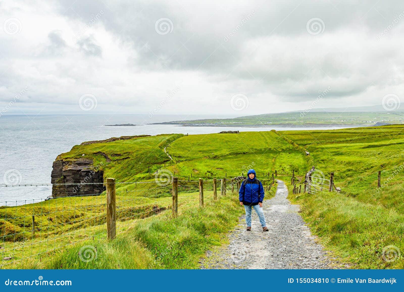 Kvinnan i det blåa omslaget som stoppar på den kust- rutten, går från Doolin till klippor av Moher