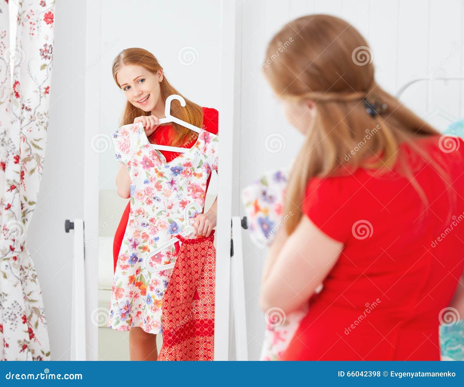 Kvinnan i en röd klänning ser i spegeln och väljer kläder