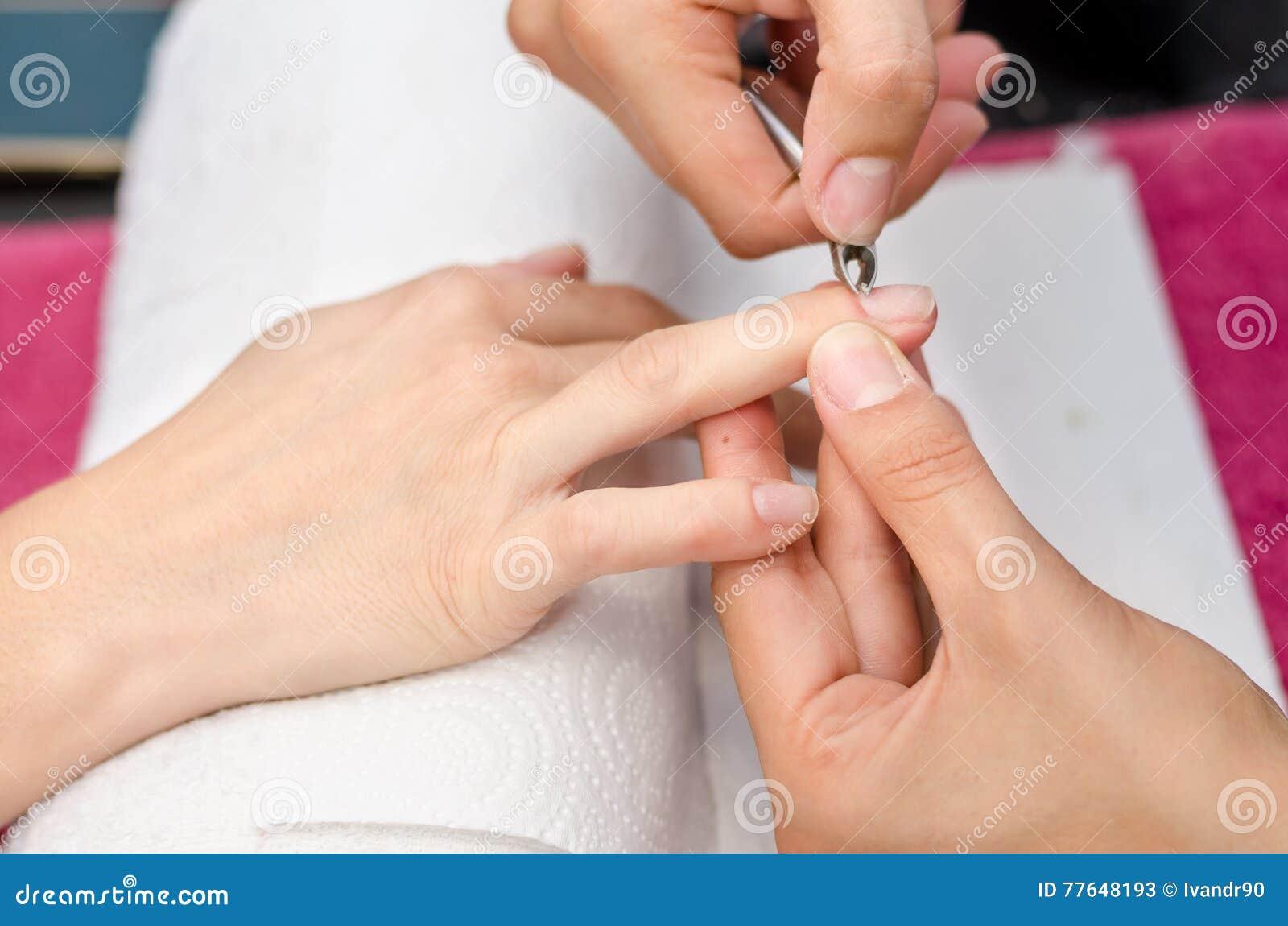 Kvinnan i salonghälerimanikyr spikar förbi kosmetologen