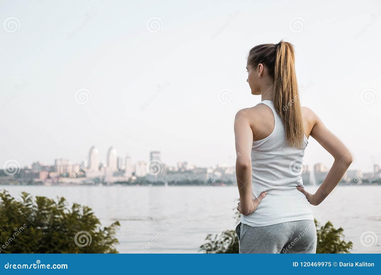 Kvinnan i sport beklär anseende på stadsbackbrounden