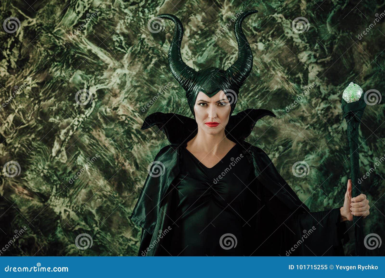 Kvinnan klädde som en felik häxa i regnrock och med horn