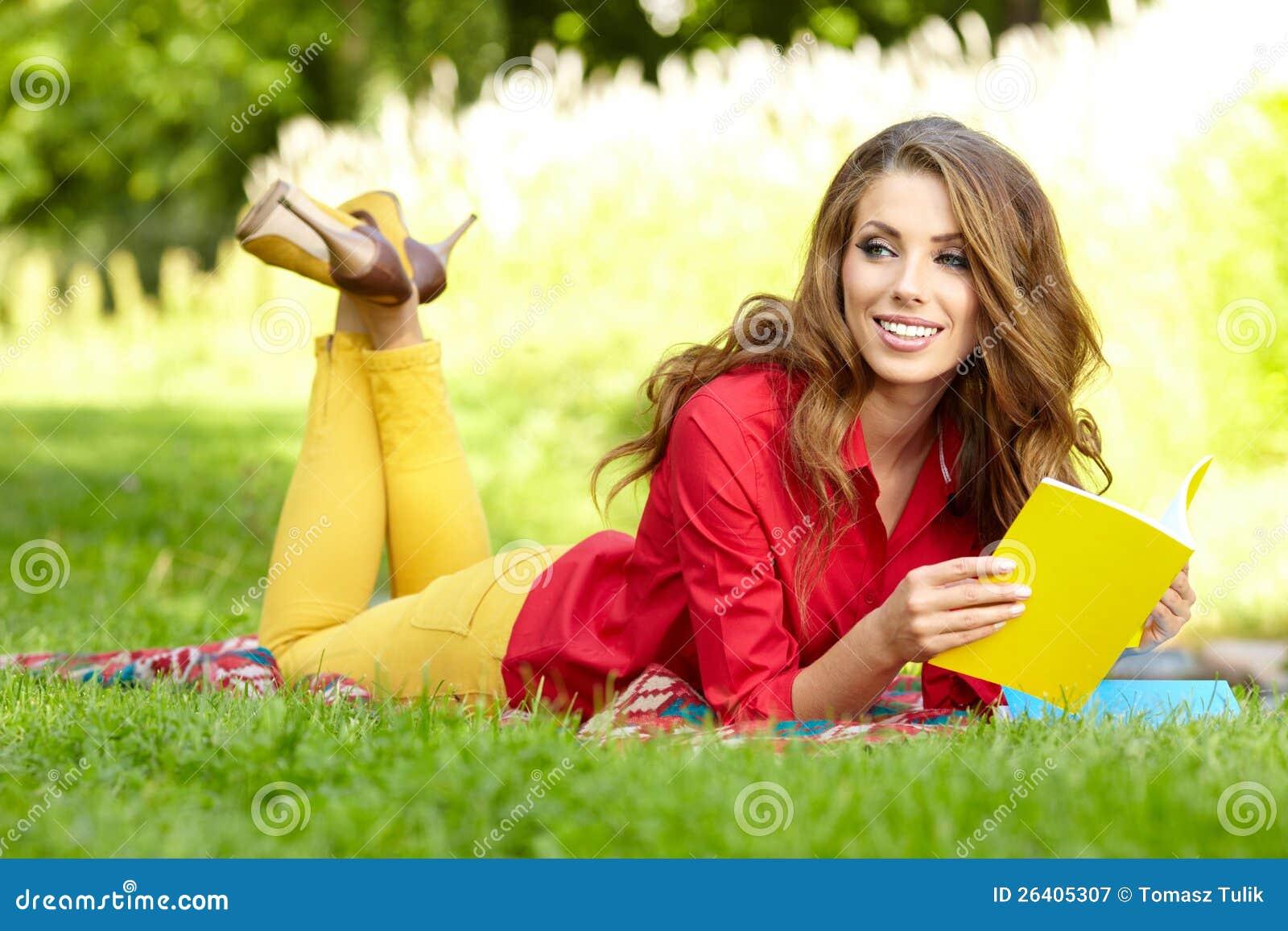 Kvinnan lägger på grönt fält och läser boken.