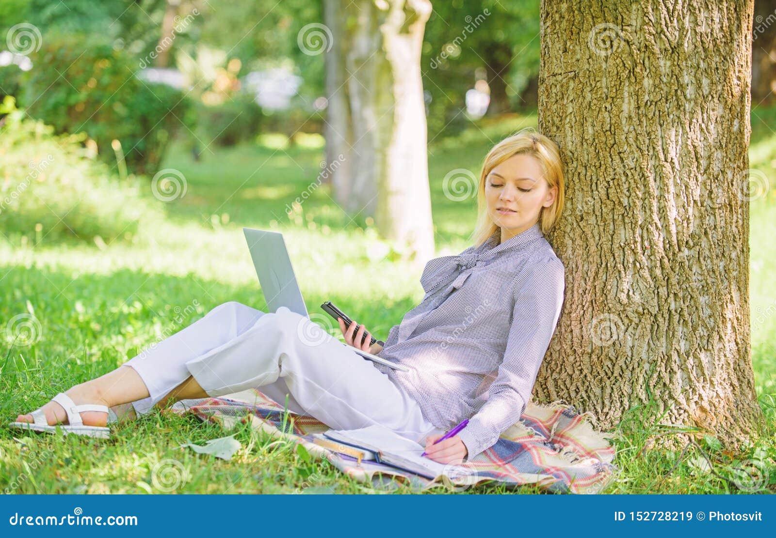 Kvinnan med arbete f?r b?rbar datordatoren lutar utomhus p? tr?dstammen Flickaarbete med b?rbara datorn i att parkera f?r att sit
