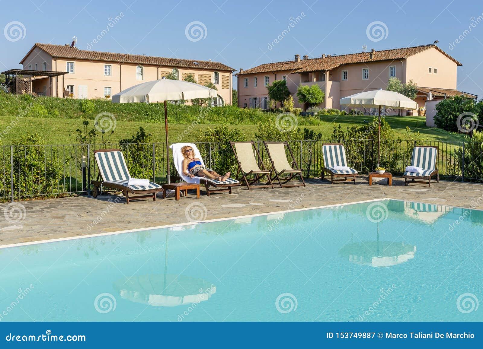 Kvinnan med solglasögon kopplar av att ligga på en dagdrivare vid pölen av en semesterort i bygden av Pisa, Tuscany, Italien