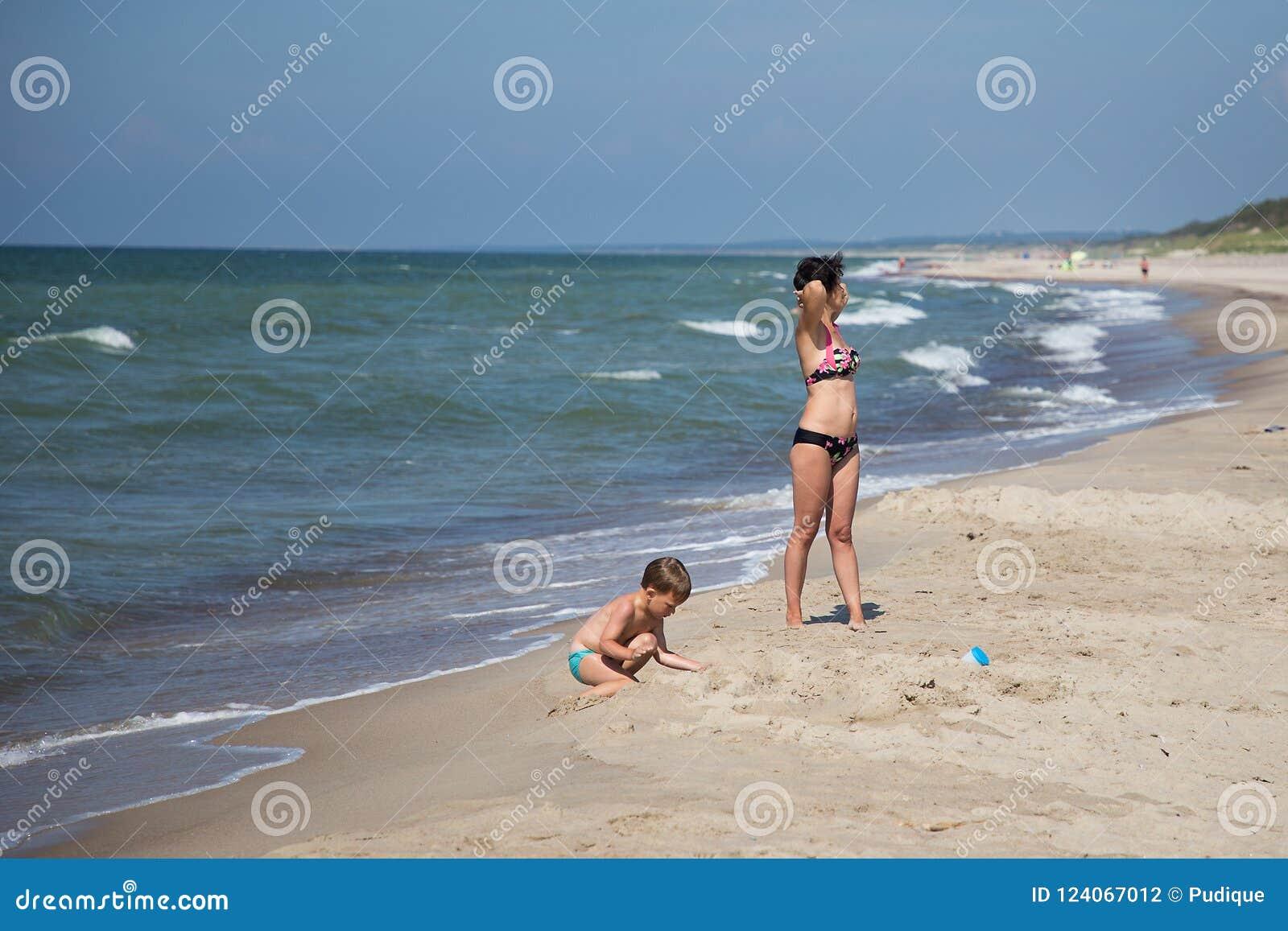 Kvinnan och barnet vilar på den baltiska stranden