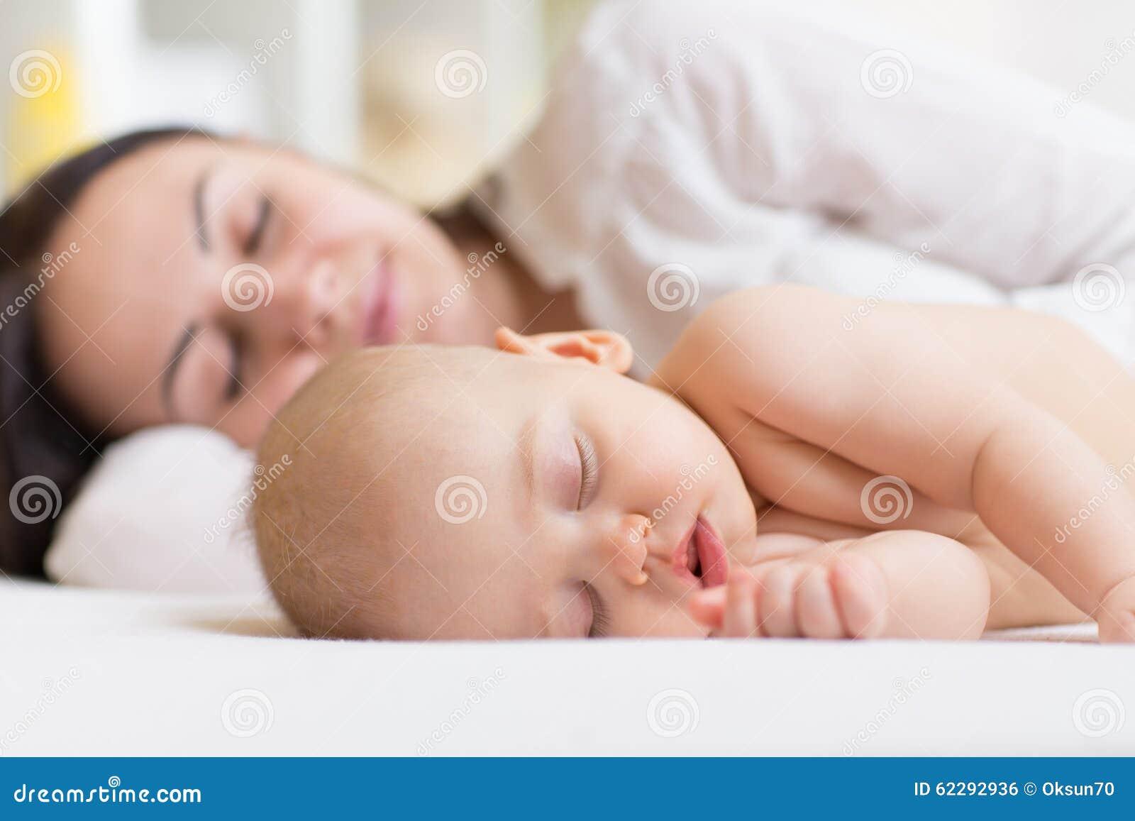 Kvinnan och behandla som ett barn pojken som kopplar av i ett vitt sovrum