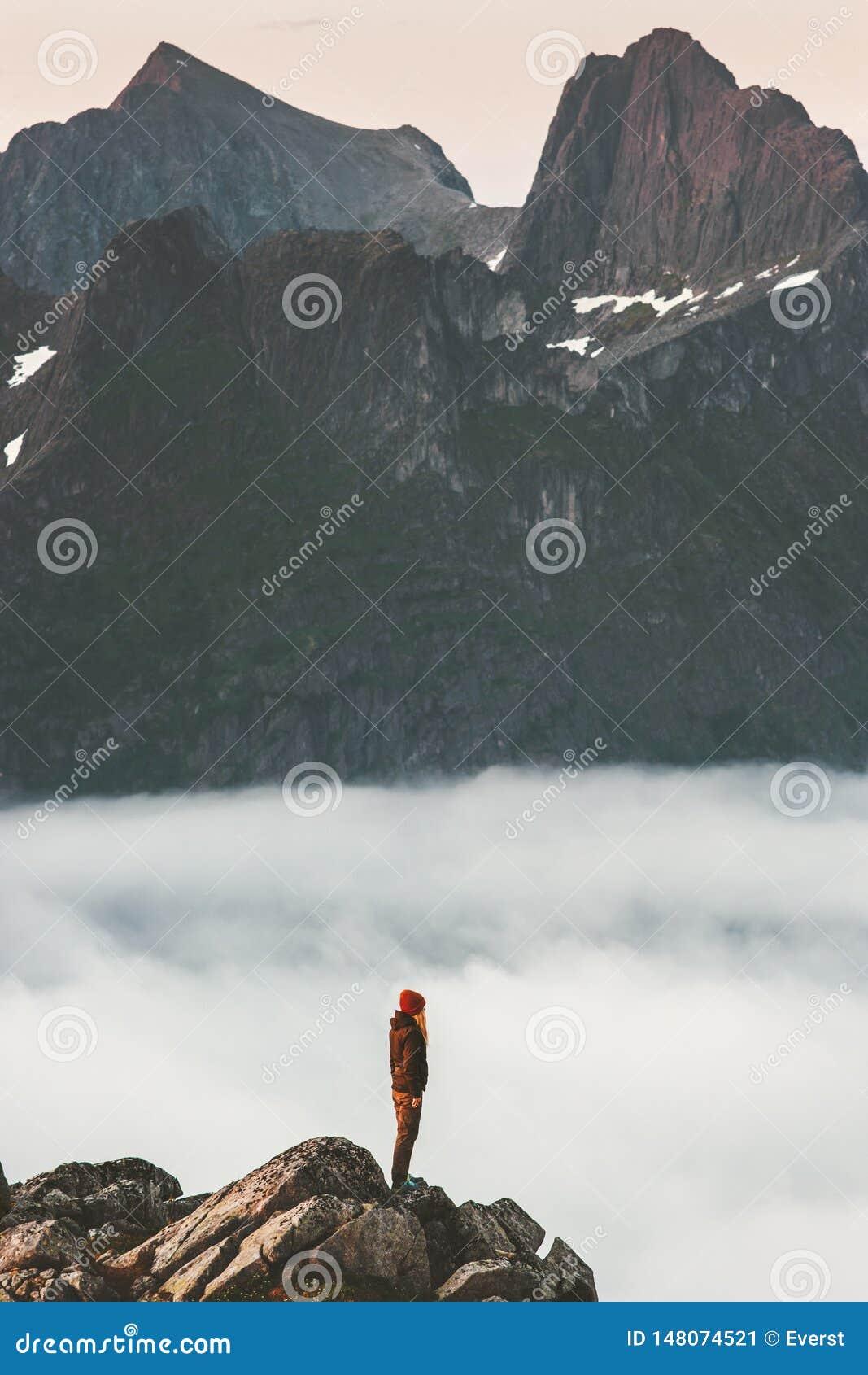 Kvinnan på klippkanten över moln reser i berg