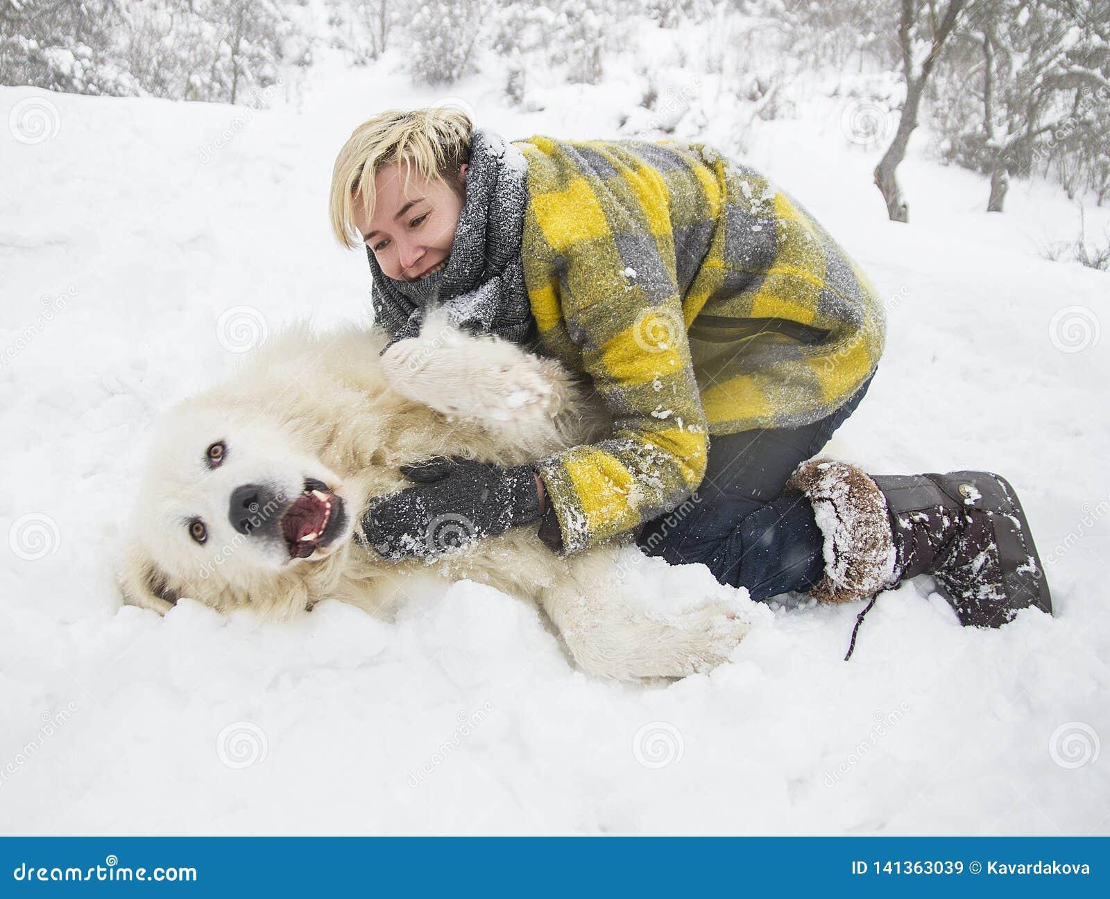 Kvinnan plaskar med en vit hund i snö