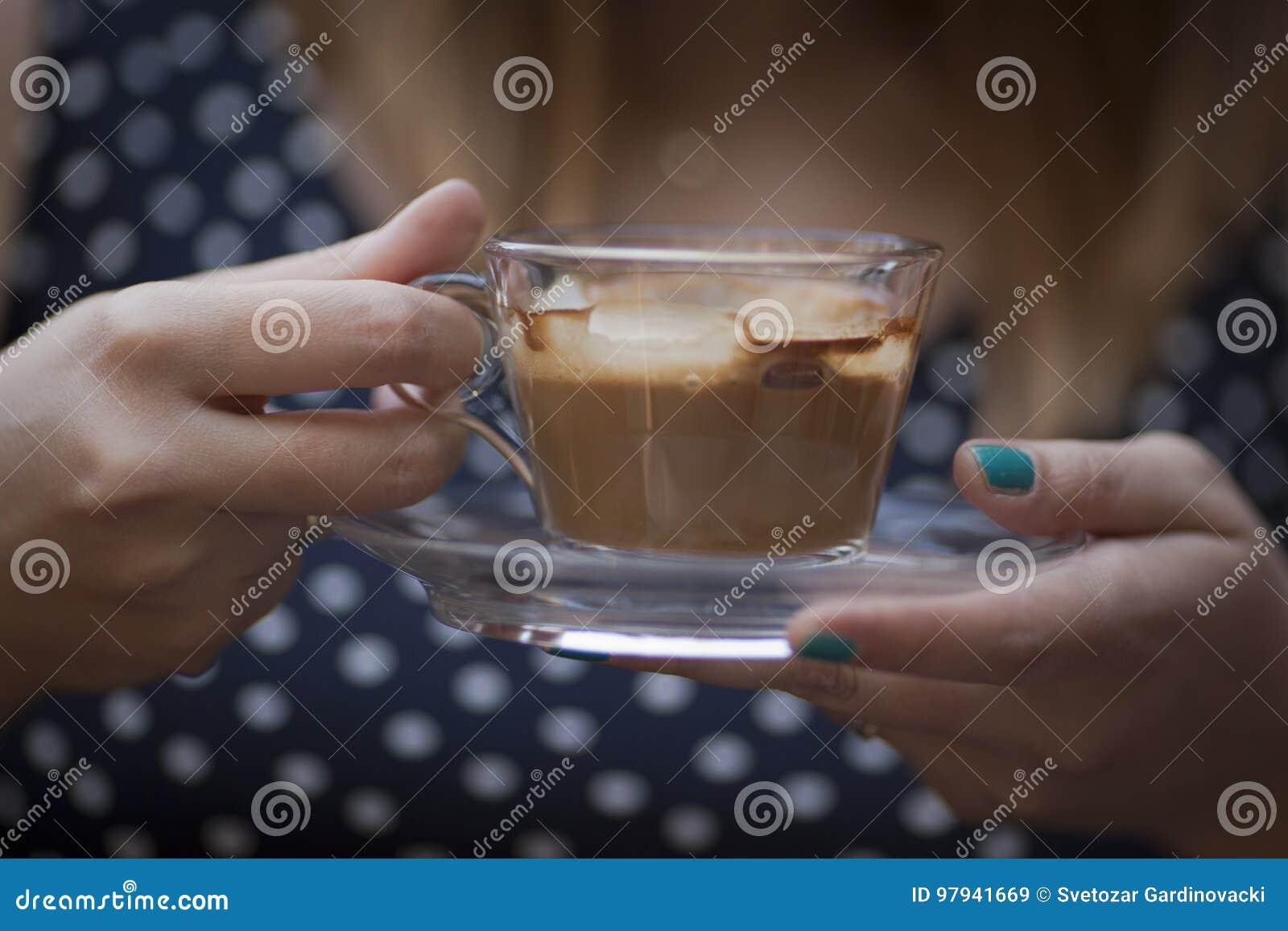Kvinnan räcker den hållande koppen kaffe
