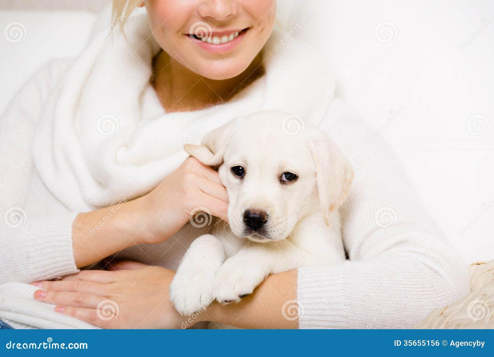 Kvinnan rymmer den labrador valpen på henne händer