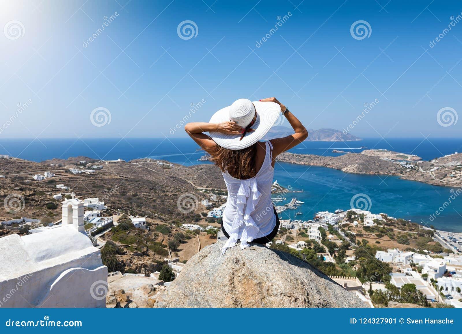 Kvinnan sitter på en vagga högt över byn av Ios-ön