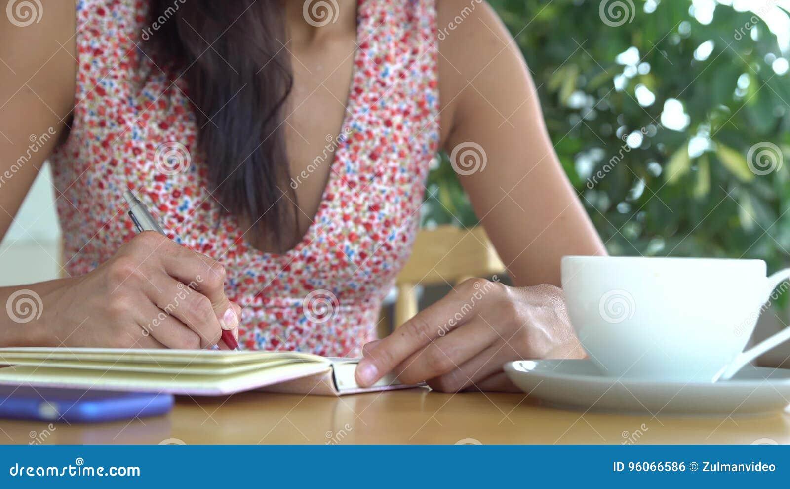 Kvinnan skriver i dagbok