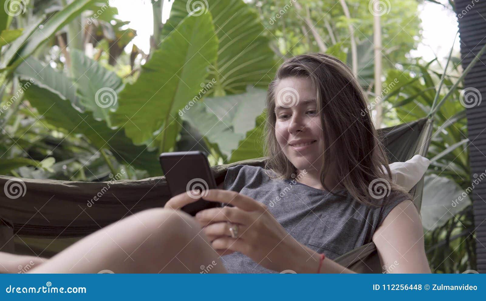 Kvinnan skriver meddelandet på smartphonen, medan sitta på hängmattan, naturlig bakgrund