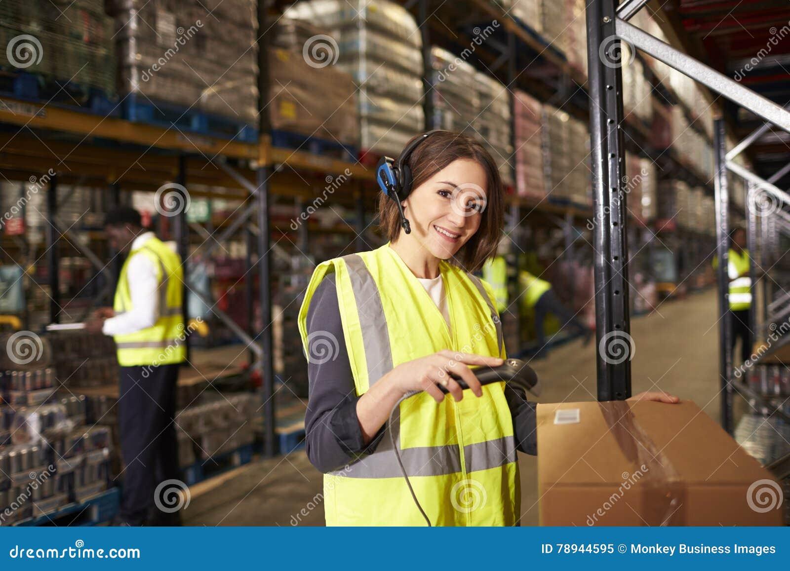 Kvinnan som använder en barcodeavläsare i ett lager, ser till kameran