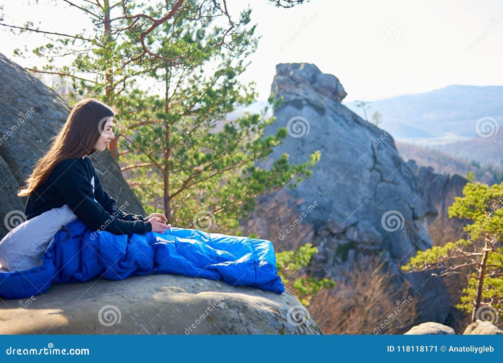 Kvinnan som bara sitter i sovsäck på det stora berget, vaggar och att le