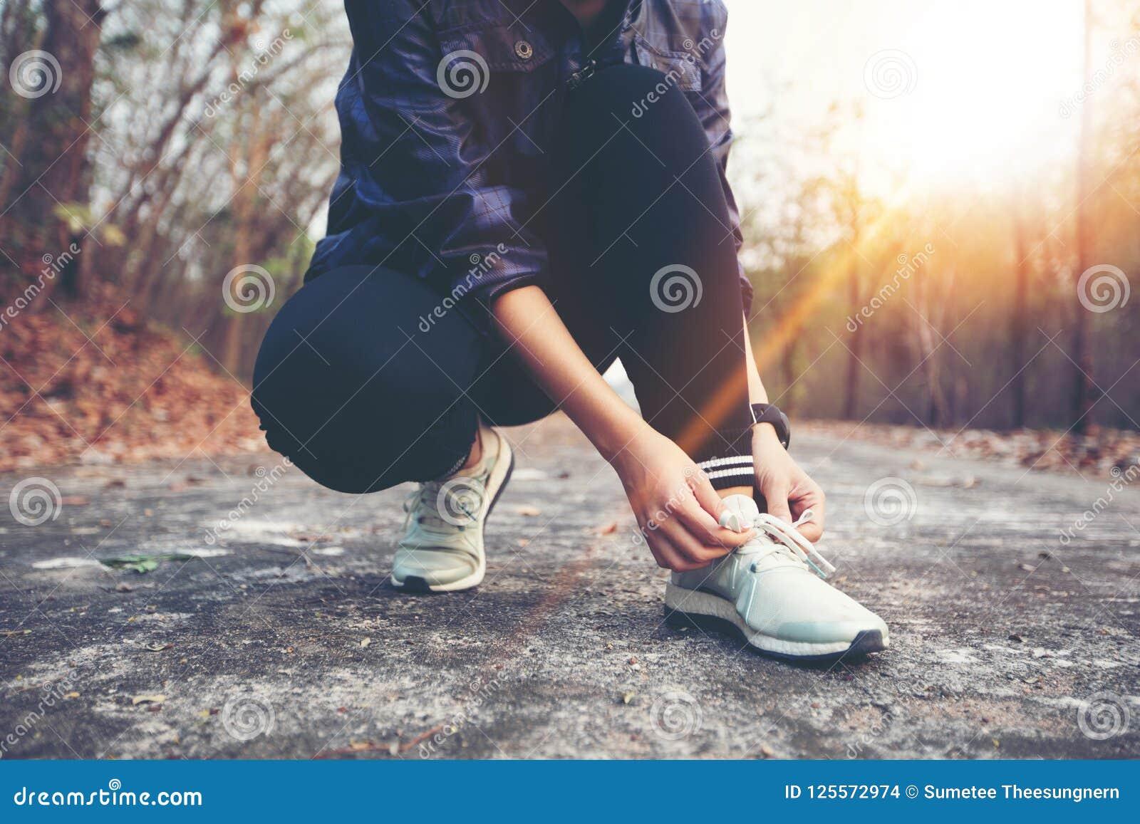 Kvinnan som binder skon, snör åt för sportkonditionlöparen som får klar fo