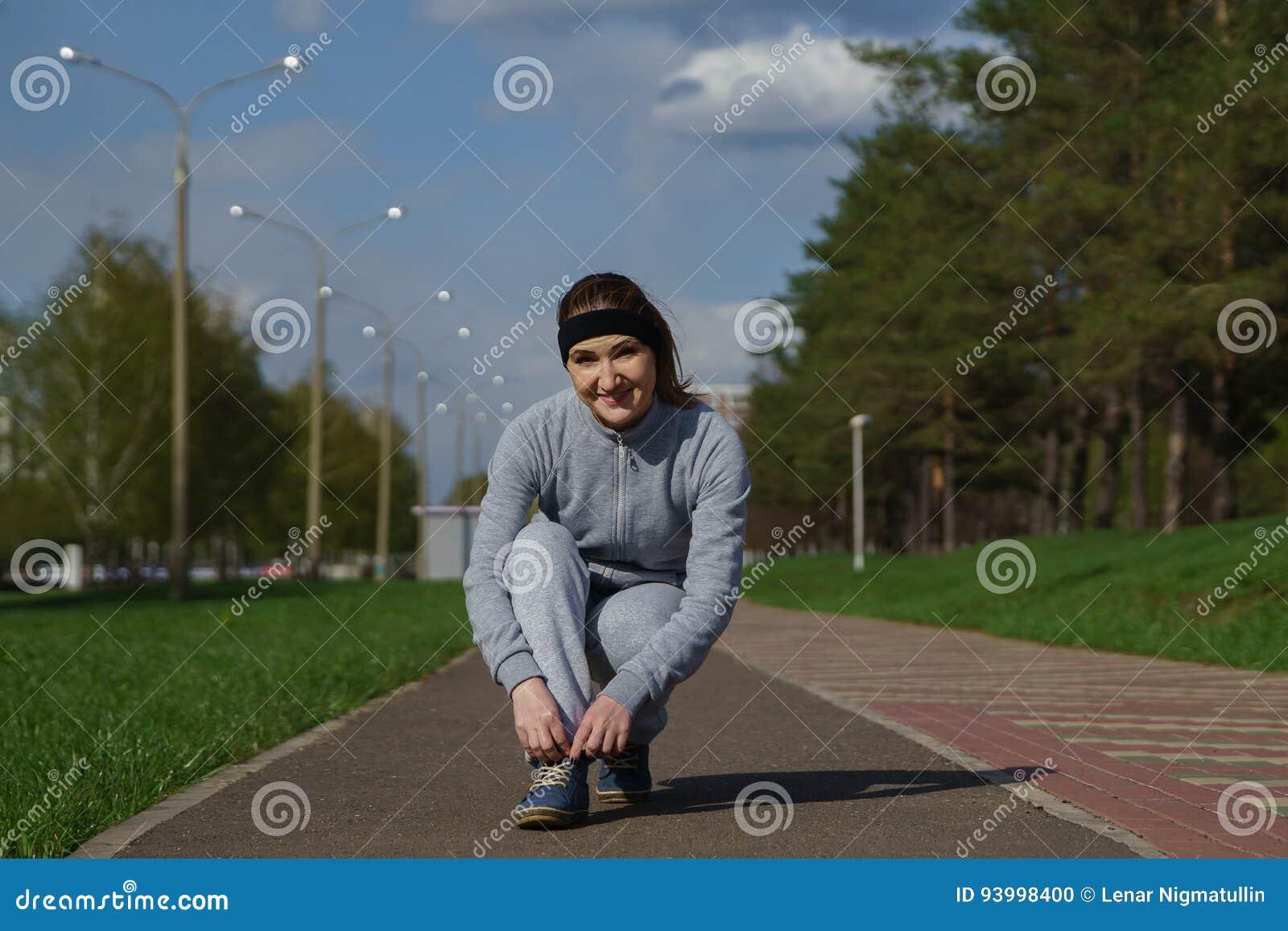 Kvinnan som binder skon, snör åt Kvinnlig sportkonditionlöpare som får klar för att jogga utomhus på skogbanan i vår eller sommar