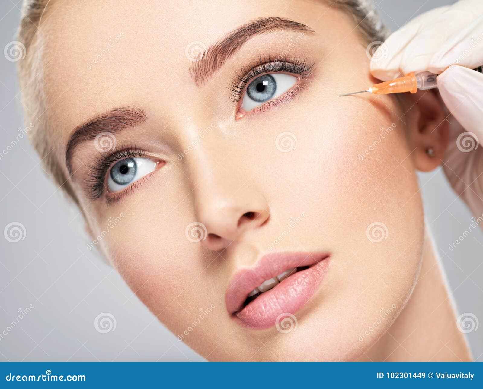 Kvinnan som får den kosmetiska injektionen av botox nära, synar