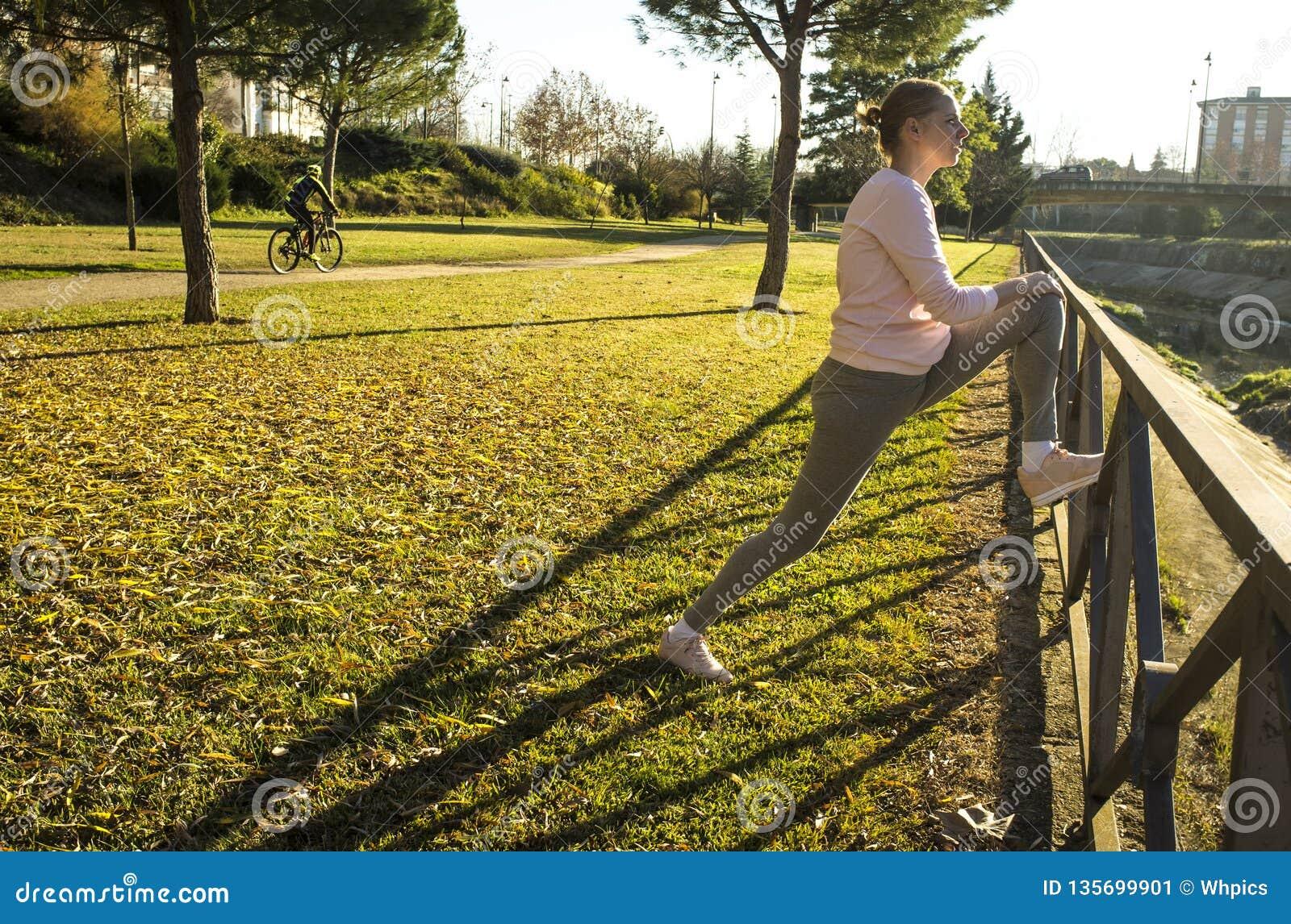 Kvinnan som gör sträcka övningar på stads-, parkerar i höstsäsong