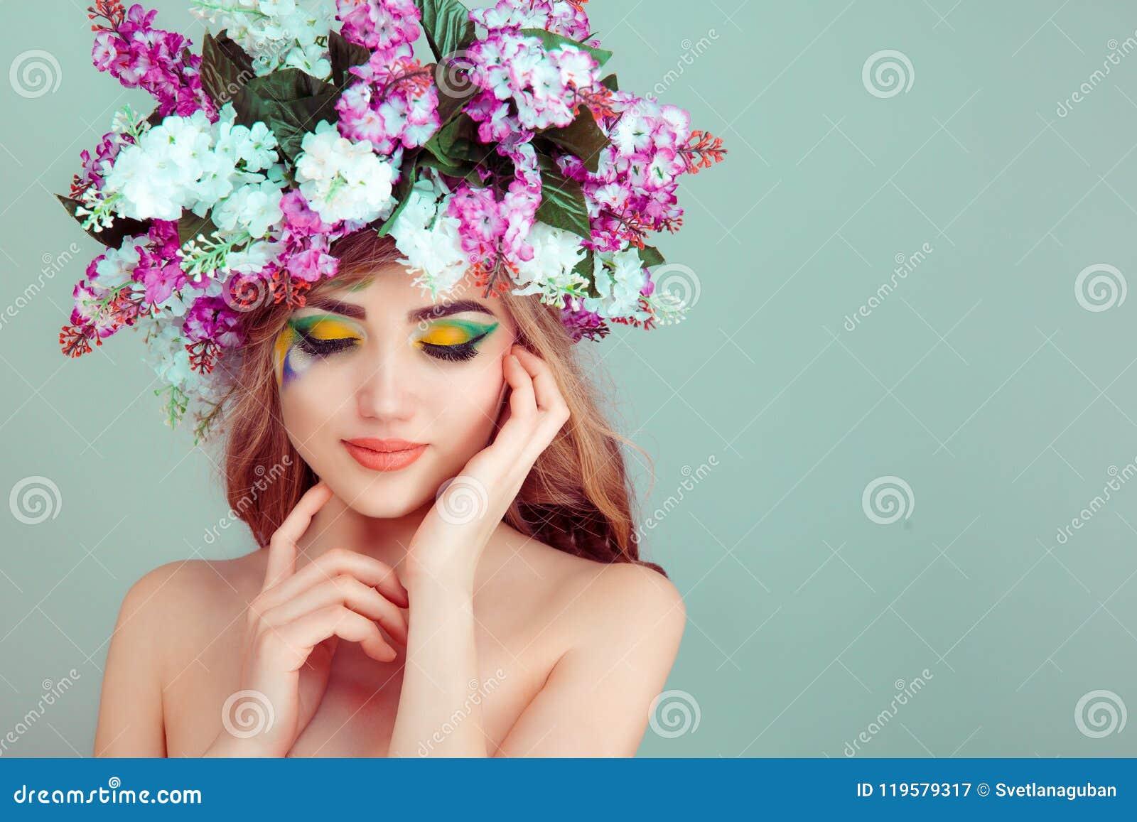 Kvinnan som ler med blommor på huvudguling- och gräsplanögonskugga, stängde ögon