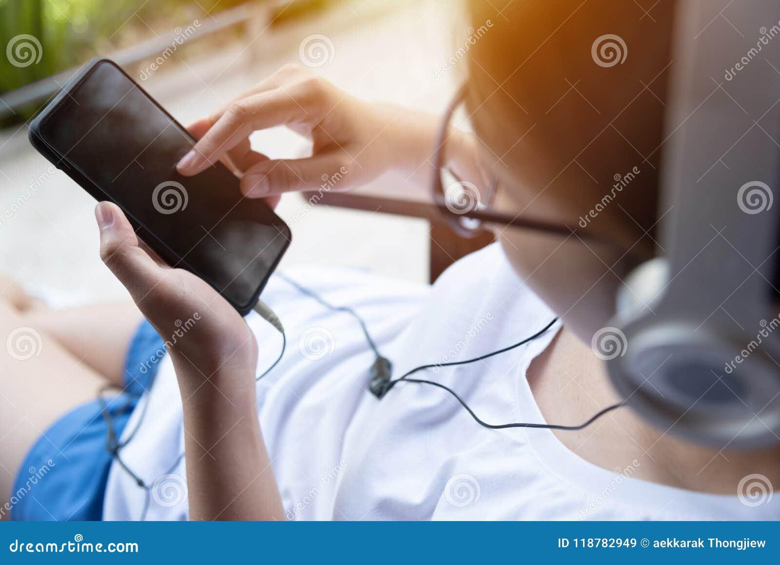 Kvinnan som lyssnar till musiken med headphonen och, ilar telefonen