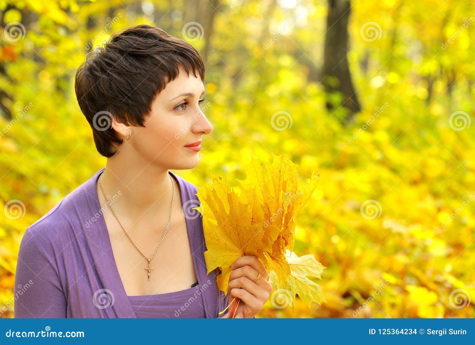 Kvinnan som rymmer en bukett av lönnlöv i en höst, parkerar