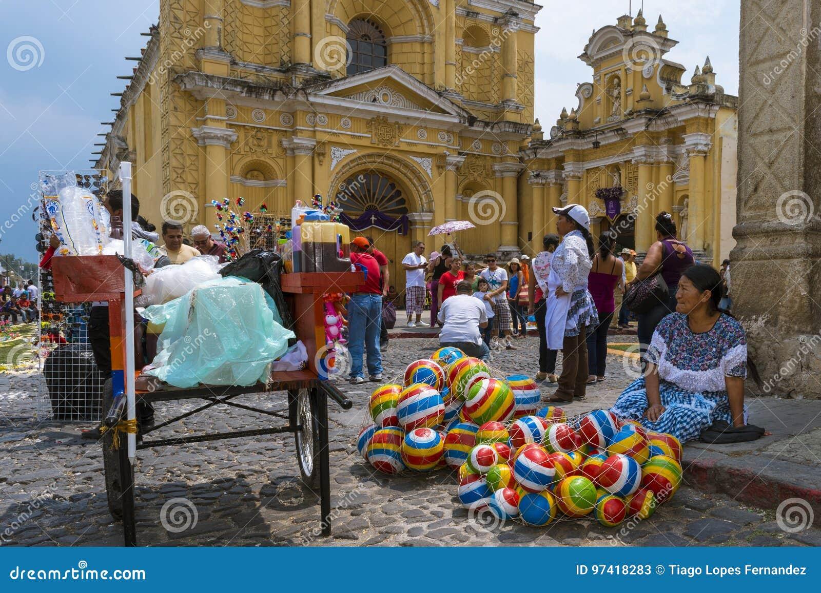Kvinnan som säljer sälja färgrikt gummi, klumpa ihop sig i en gata av den gamla staden av Antigua med Sanen Pedro Hospital på bak