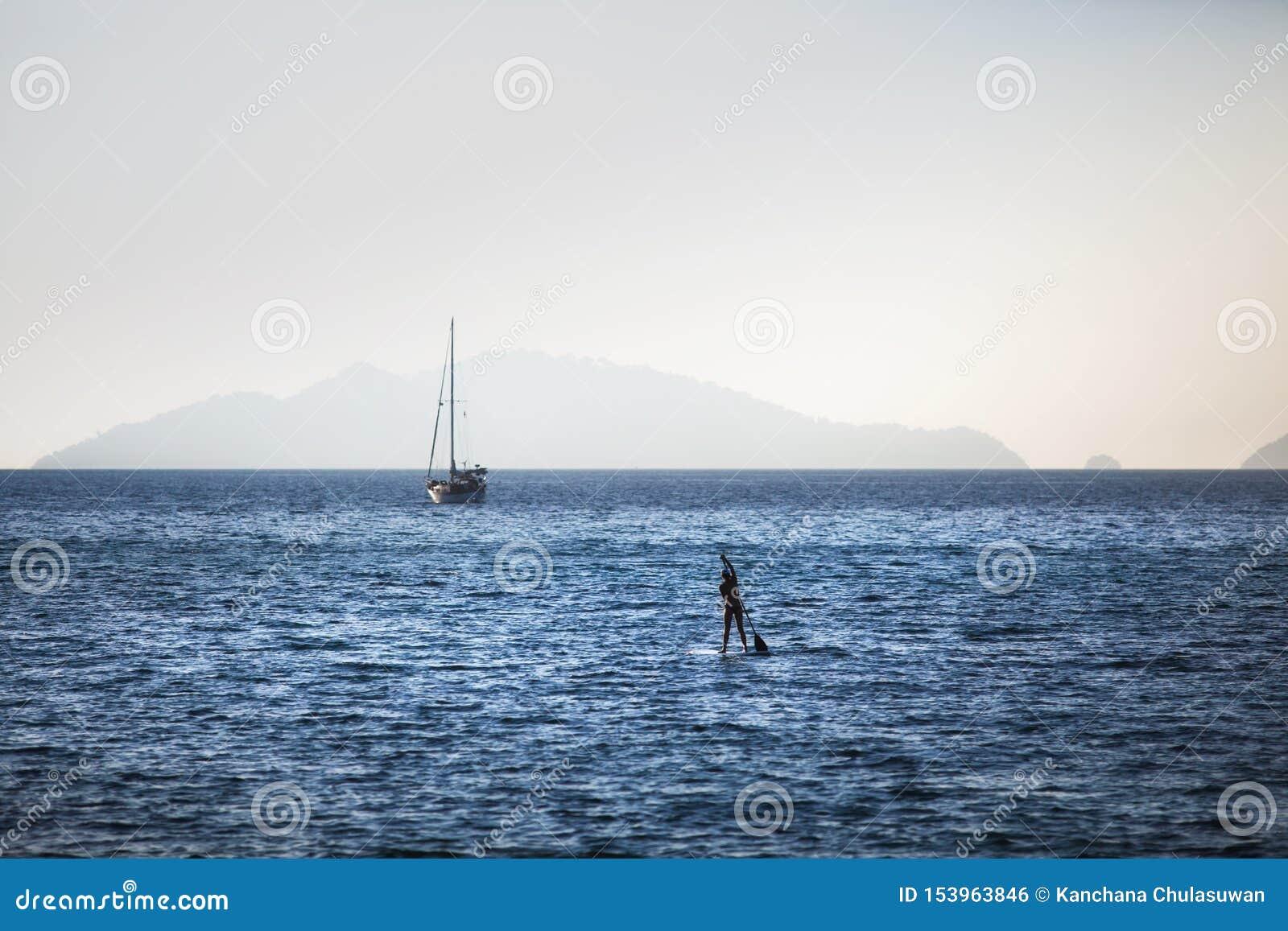 Kvinnan står upp skovellogi på ett ursprungligt hav på Koh Lipe
