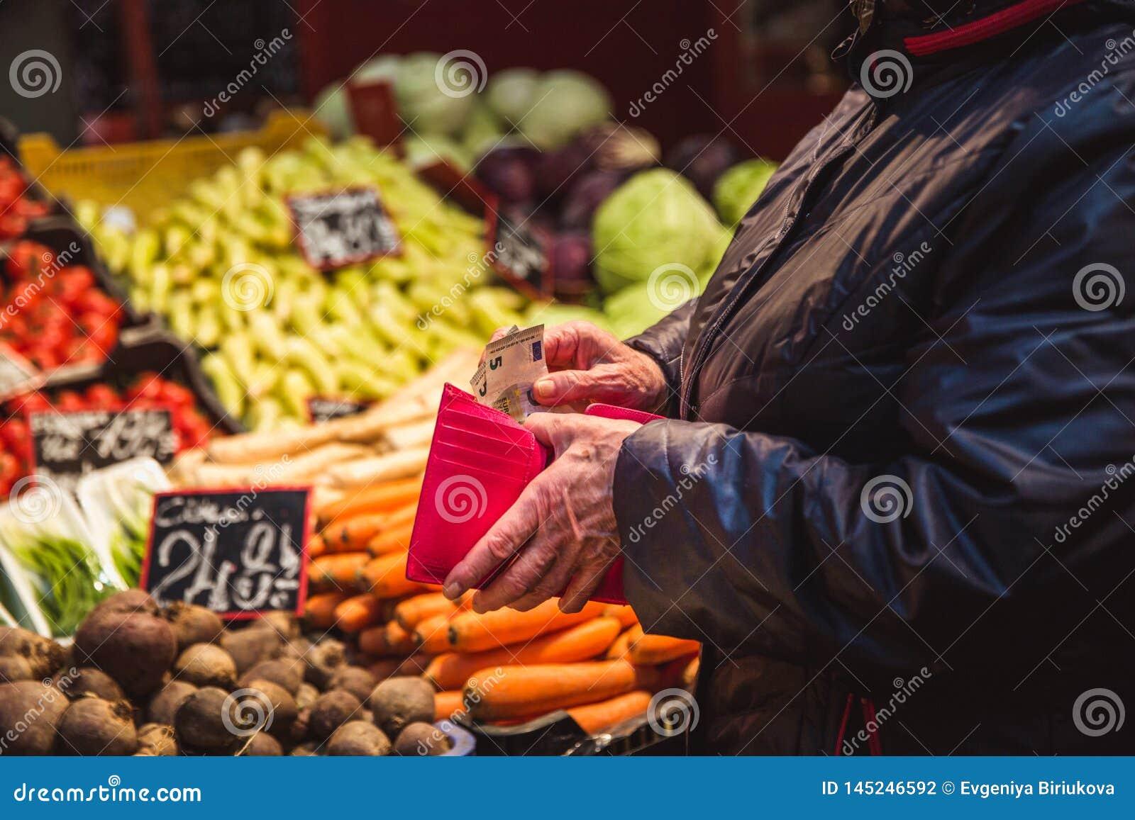Kvinnan tar pengar ut från plånboken på marknad