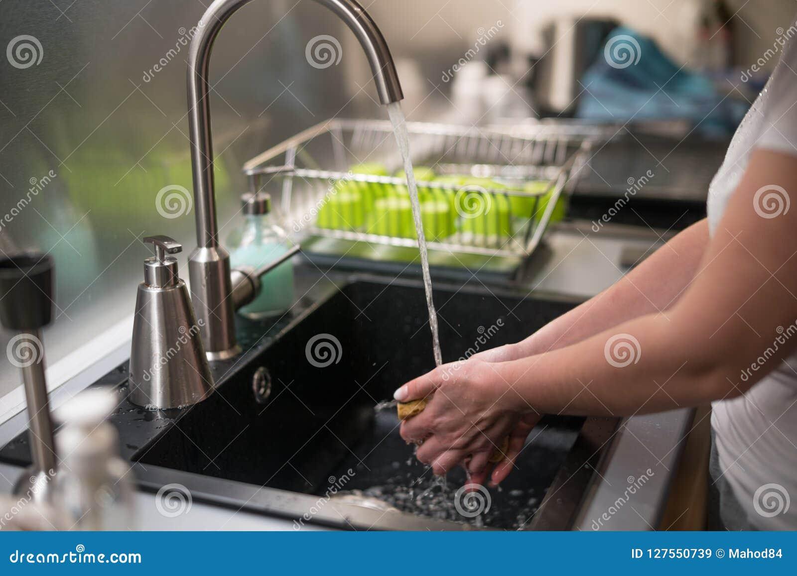 Kvinnan tvättar hennes händer i vasken