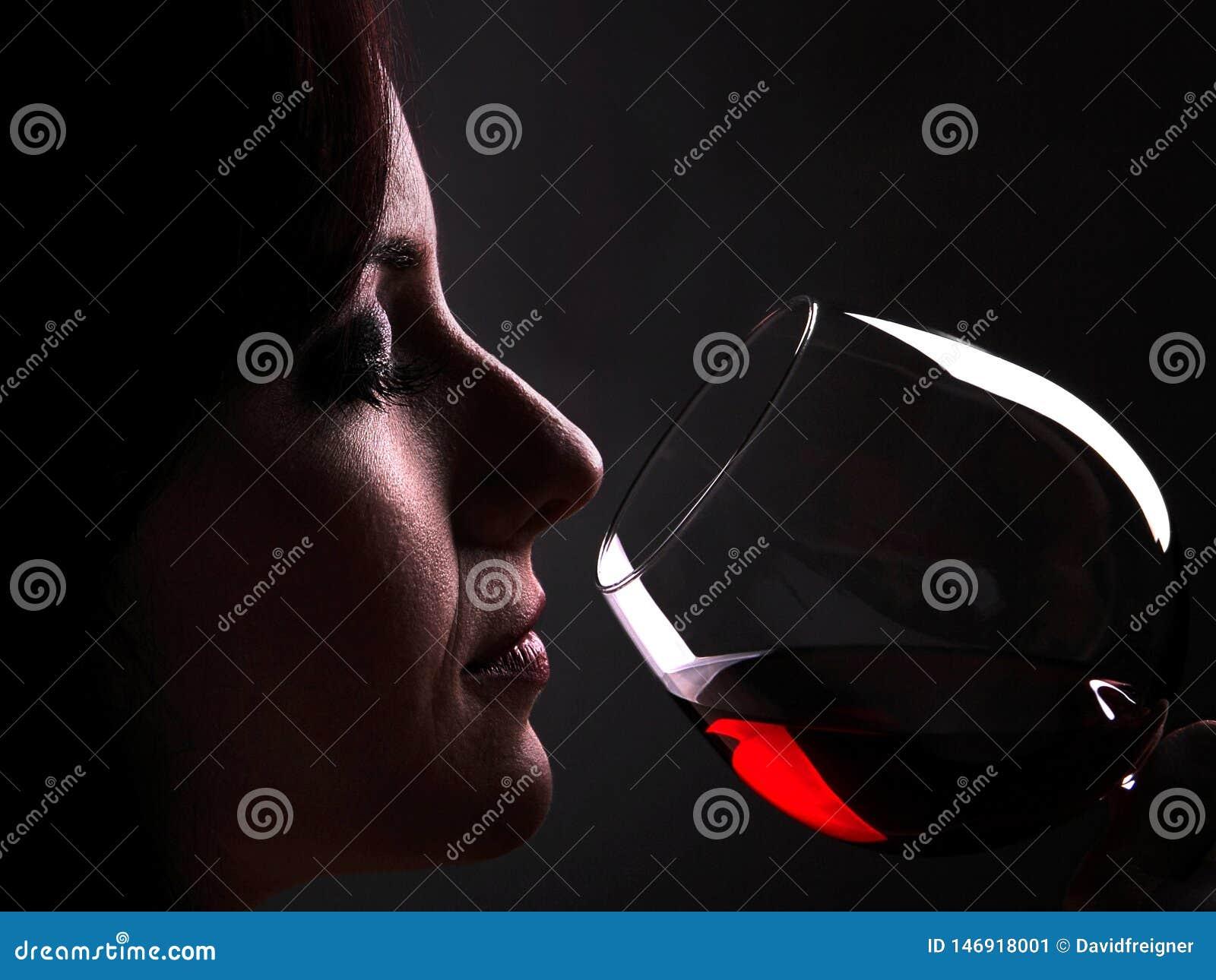 Kvinnan tycker om smaken och buketten av ett exponeringsglas av rött vin