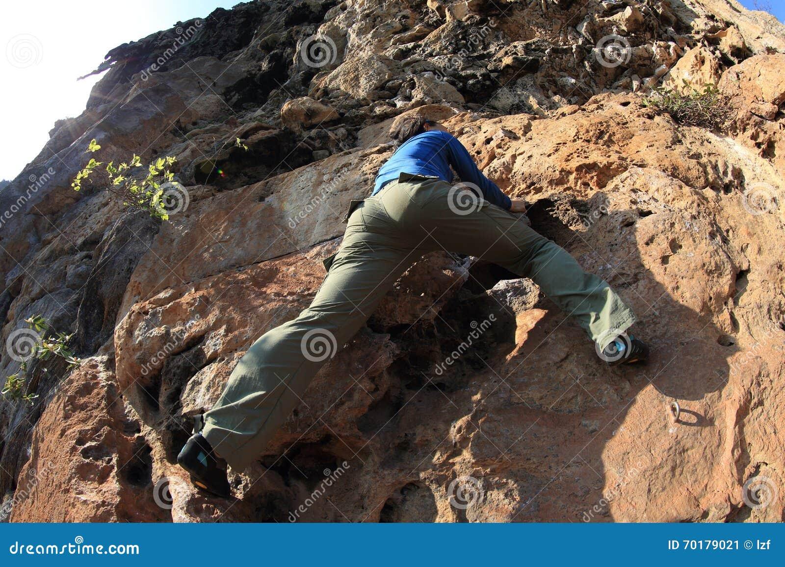 Kvinnan vaggar klättrareklättring på sjösidabergklippan