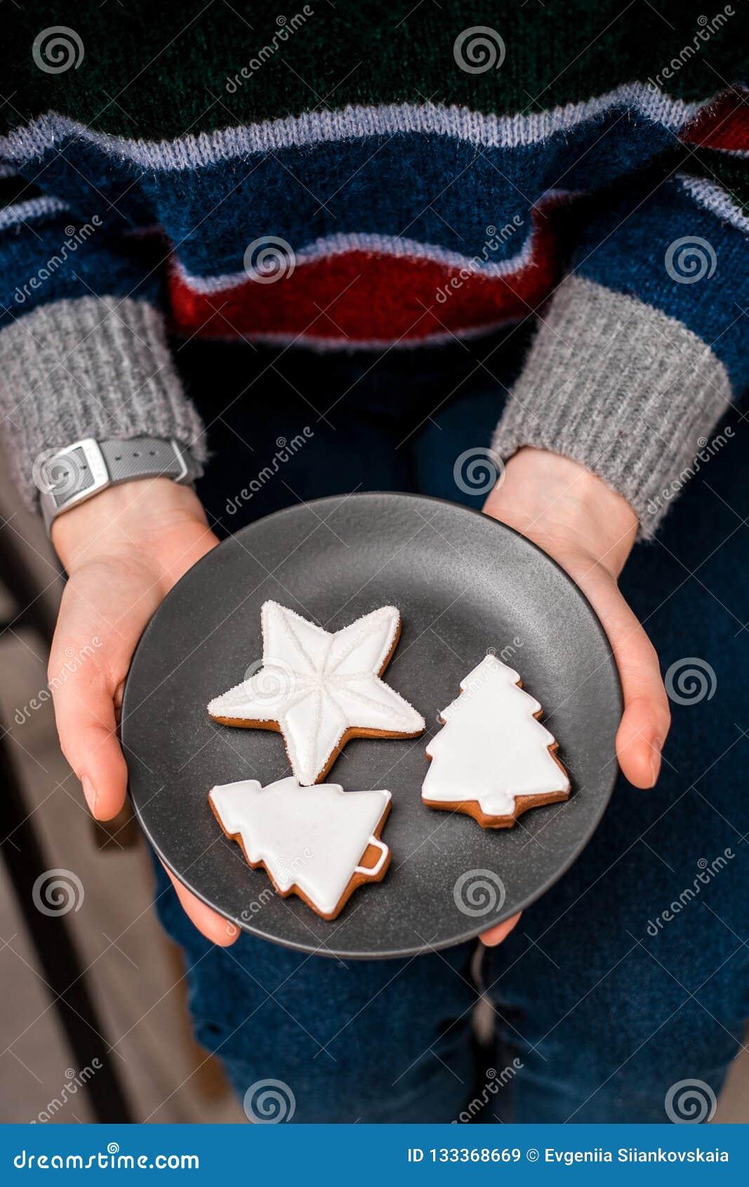 Kvinnans händer rymmer plattan med julkakor